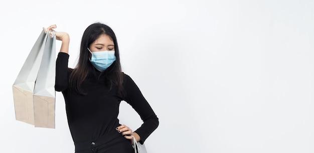 買い物袋を手に持ち、医療用フェイスマスクを身に着けているアジアの女性