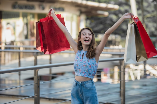 Asian woman holding shopping bags and raised hands up
