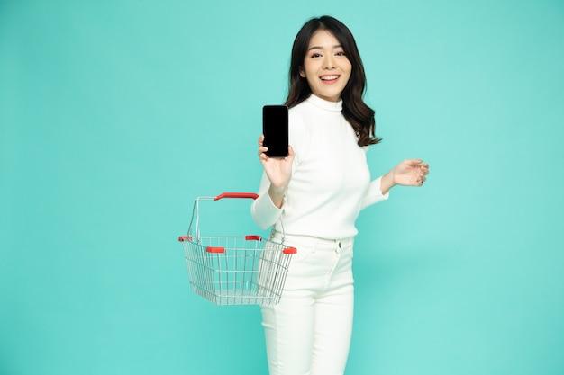 Азиатская женщина, держащая корзину для покупок и показывающая мобильный телефон на светло-зеленом фоне