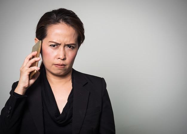 Asian woman holding smart phone in angry and boring emotion.