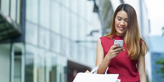 Asian woman holding smartphone with shopping bags