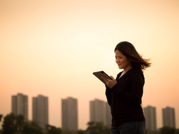 일몰 하늘 배경으로 태블릿을 들고 아시아 여자