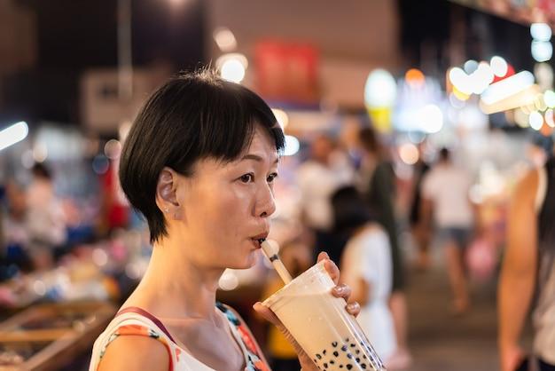 Азиатская женщина держит знаменитый тайваньский пузырьковый чай с молоком на ночном рынке