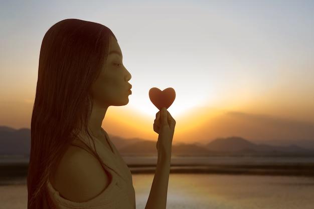Азиатская женщина держит красное сердце на фоне закатного неба. день святого валентина