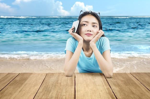 푸른 하늘을 배경으로 해변 테이블에 기대어 티켓과 여권을 들고 있는 아시아 여성