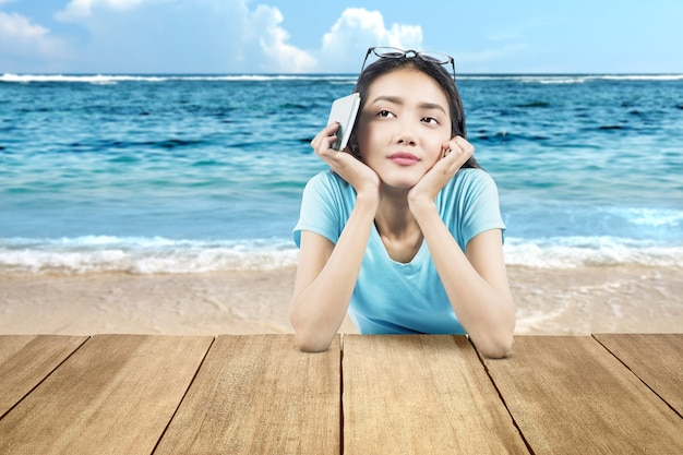 Asian woman holding ticket and passport leaning on beach table with a blue sky background