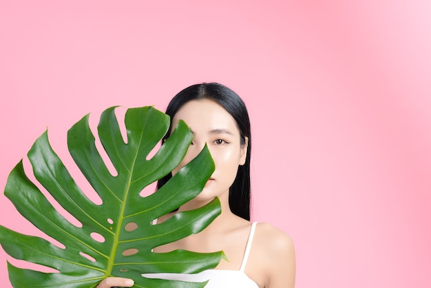 Asian woman holding a tropical leaf with natural skin on pink