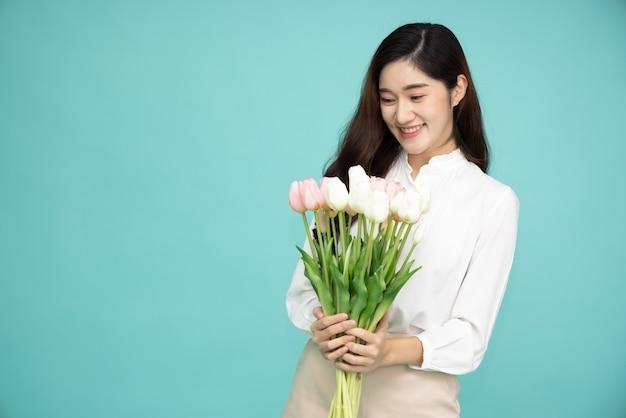 녹색 표면 위에 절연 튤립 꽃을 들고 아시아 여자