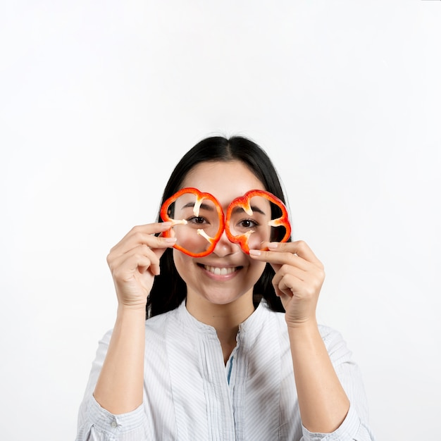 Asian woman holding two slices of red bell peppers in front of her eyes above white surface