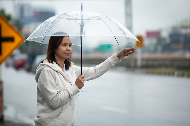 Asian woman holding umbrella hitchhiking taxi at city street in the rainy day.