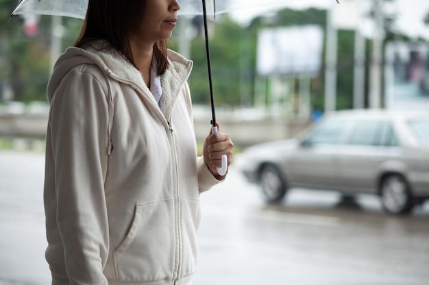 雨の日にタクシーを待っていると都市の歩道に立っている間傘を保持しているアジアの女性。