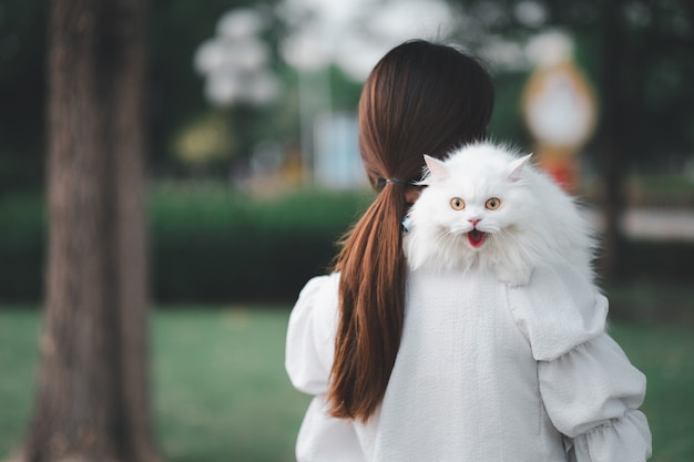 Asian woman holding a white cat in a park