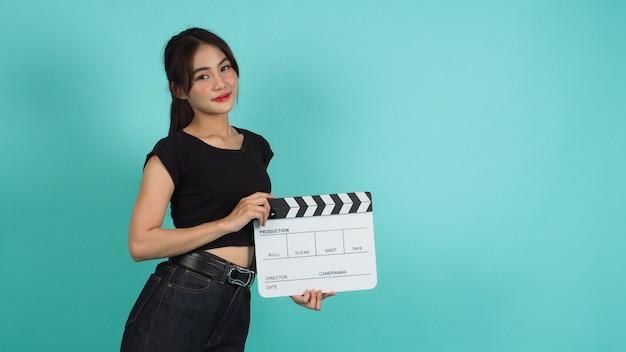 녹색 민트나 티파니 블루 배경에 흰색 클래퍼보드나 영화 슬레이트를 들고 있는 아시아 여성.