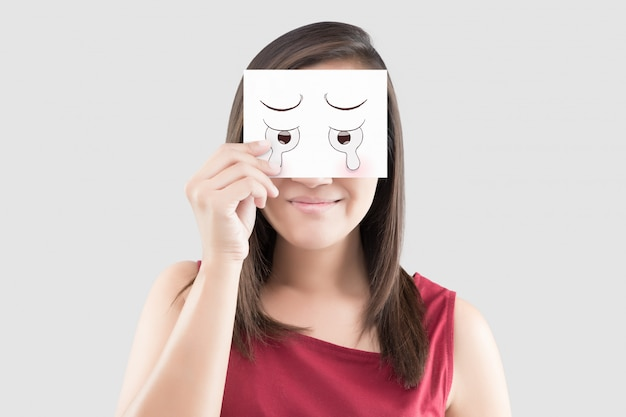 Asian woman holding a white paper with a cartoon cry face on it in front of her eyes