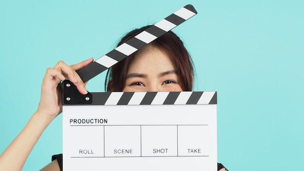 화이트클래퍼보드를 들고 민트나 티파니 블루 배경에 얼굴을 감고 있는 아시아 여성.