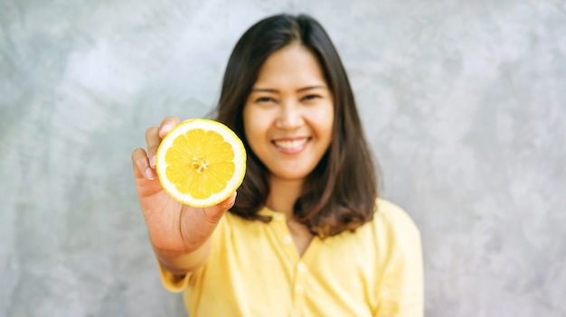 Asian woman holding a yellow lemon, selective focus.