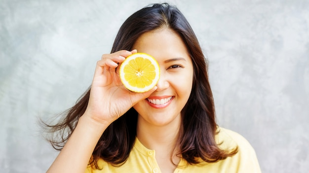 Asian woman holding a yellow lemon