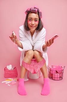 아시아 여성은 위생적인 탐폰을 들고 현대적인 스마트폰을 사용하여 곱슬 머리에 컬러를 바르고 눈 아래 하이드로겔 패치를 적용하여 변기에 자신을 드러냅니다. 흰색 목욕 가운 양말 레이스 팬티