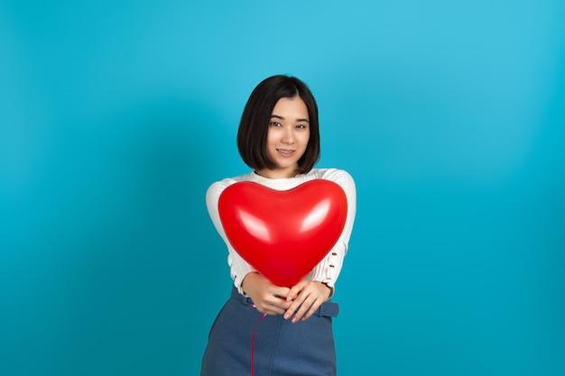 Азиатская женщина протягивает красный воздушный шар в форме сердца