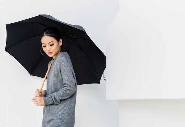 白い背景に傘を持つアジア人女性