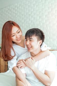 アジアの女性は彼らの寝室で彼女のボーイフレンドを抱擁、素敵なアジアカップルのコンセプト