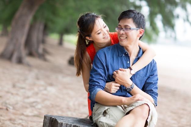 アジアの女性は、ビーチで一緒に笑顔で見ている彼女のボーイフレンドを抱きしめます。