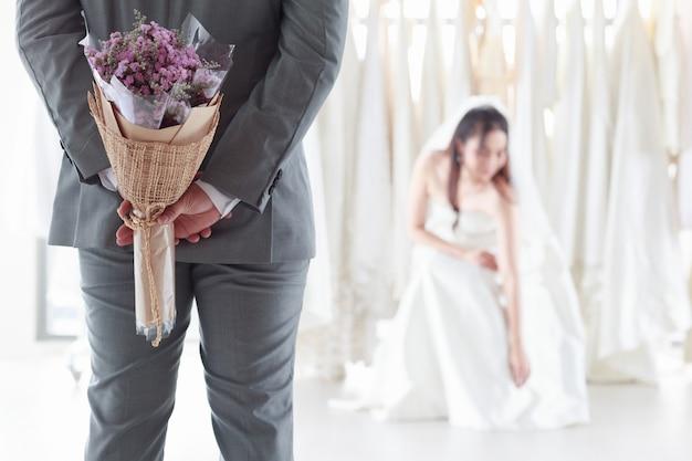 신부 가운에 아시아 여자 웃는 신랑. 회색 양복을 입은 신랑은 보라색 꽃다발을 들고 피팅룸에 앉은 신부를 놀라게 한다. 컨셉 웨딩 최고의 날.