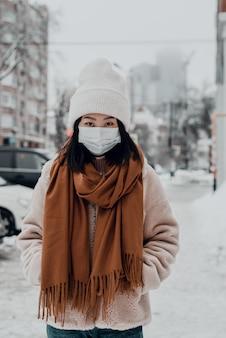 Азиатская женщина в защитной маске, прогуливаясь по заснеженной улице. концепция коронавируса в повседневной жизни