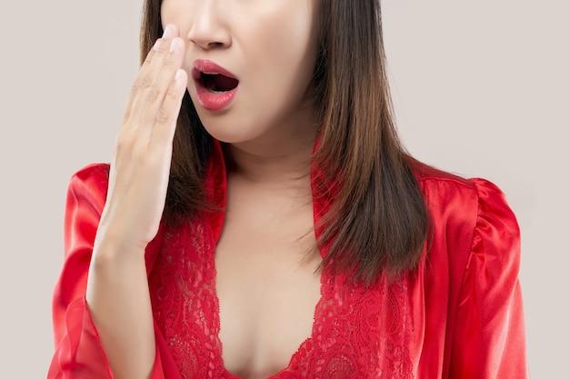 Азиатская женщина в красном атласном халате делает тест на дыхание рукой