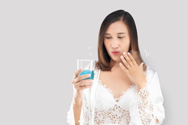 레이스 가운을 입고 새틴 흰색 잠옷을 입은 아시아 여성이 구강 세척제를 사용하기 때문에 입안에 화상을 느낍니다.