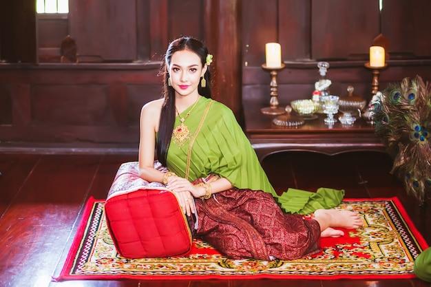 伝統的なタイのドレスを着て、タイ風の木造家屋に座っているアジアの女性。