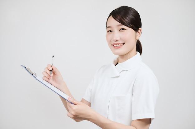 Азиатская женщина в белом халате заполняет медицинскую карту