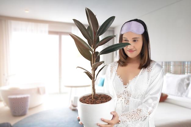 Азиатская женщина в белой атласной ночной рубашке носить кружевной халат, держа каучуковое растение в белом горшке.