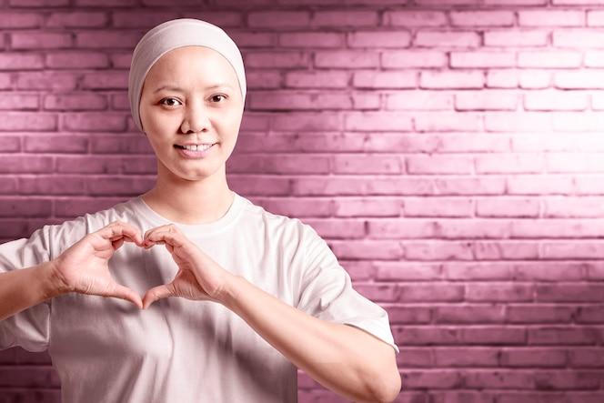 그녀의 손으로 심장 기호를 보여주는 흰 셔츠에 아시아 여자. 유방암 인식