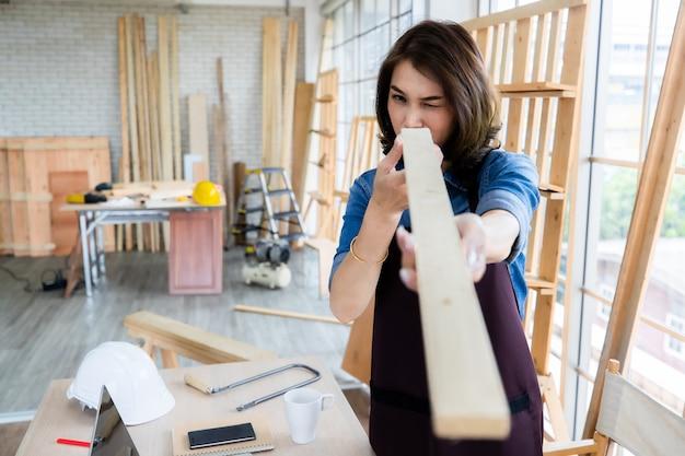 Азиатская женщина в фартуке осматривает доску пиломатериалов, стоя возле стола в просторной профессиональной мастерской