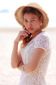 Азиатская женщина в красивой шляпе на тропическом пляже