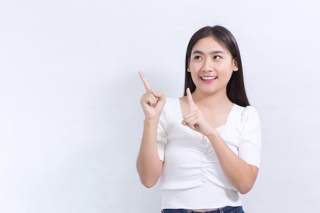 黒の長い髪のアジアの女性は白いシャツを着て、白い背景に何かを提示するためにポイントを示しています。