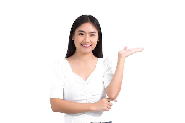 黒の長い髪のアジアの女性は白いシャツを着て、何かを提示するためにポイントを示しています