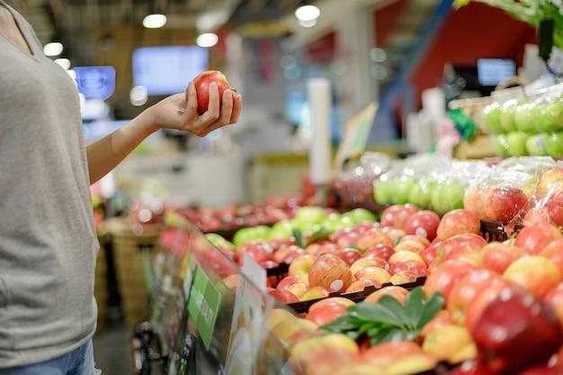 スーパーマーケットでの買い物カジュアル服でアジアの女性