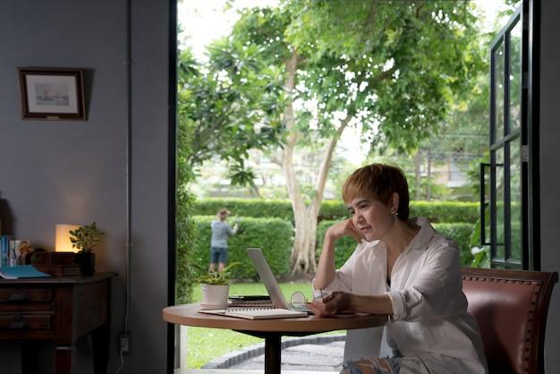 Азиатская женщина в повседневной одежде, используя ноутбук, работающих в помещении на дому