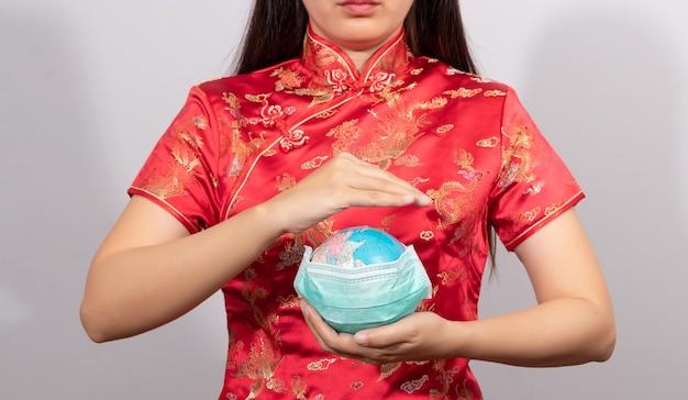 Азиатская женщина в костюме китайца держа глобус носит гигиеническую маску в руке для предотвращает жест. заболеваемость в мире вспышкой инфекции коронавирус 2019 или концепции covid-19.