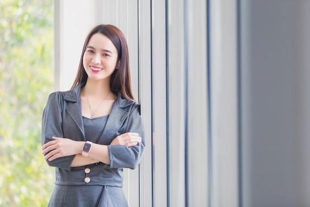 짙은 회색 드레스를 입은 아시아 여성은 행복하게 웃고 직장의 회색 커튼 옆에 서 있습니다.
