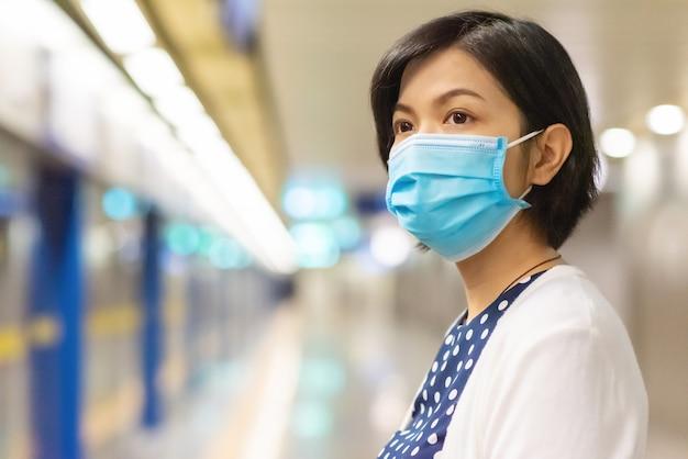 働くために旅行のためにメトロを待っているフェイスマスクのアジア女性