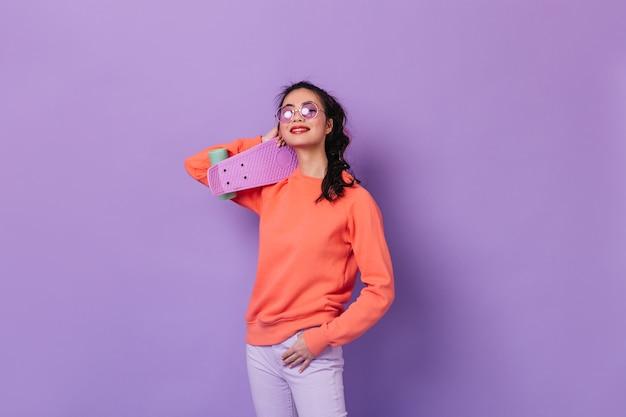 Longboard를 들고 안경에 아시아 여자입니다. 보라색 배경에 고립 된 스케이트 보드와 일본 여자의 스튜디오 샷.