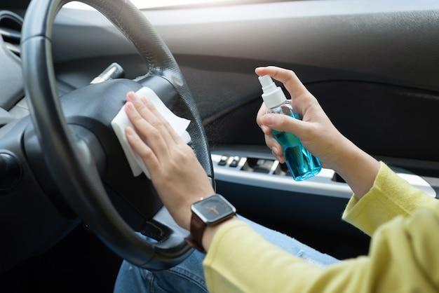 緑のシャツを着たアジア人女性が消毒用アルコールスプレーとステアリングホイールの白い布拭きを使用して、車内でのコロナウイルスまたはコロナウイルスの流行を防ぎます。