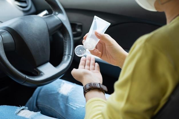 Азиатская женщина в зеленой рубашке с помощью дезинфицирующего средства для рук спиртового геля моет и чистит руки для предотвращения covid-19 или coronavirus перед вождением автомобиля.