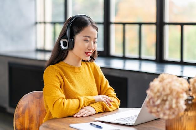 사무실에서 노트북에 전화 회의 및 화상 채팅으로 말하는 헤드셋에 아시아 여자