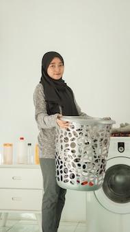 ヒジャーブのアジアの女性は家で洗うために服のバスケットを持ってきます