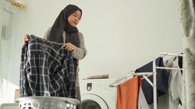自宅で洗濯物を乾かすヒジャーブのアジアの女性