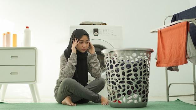 Азиатская женщина в хиджабе устала от стирки дома